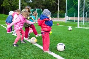 Barn vid fotbolls mål sparkandes på fotbollar