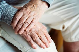 Bild på två händer, äldre. Placerade i ett knä