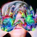 Barn med målarfärg på händerna och håller dem för ansiktet för ansiktet