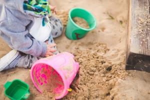 Barn med två hinkar i sandlåda