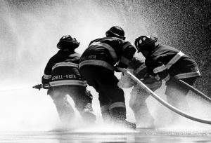 Svart/grå bild på brandmän som släcker en eld