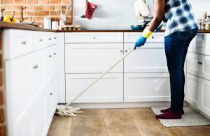 Person som skurar ett golv med golvmopp