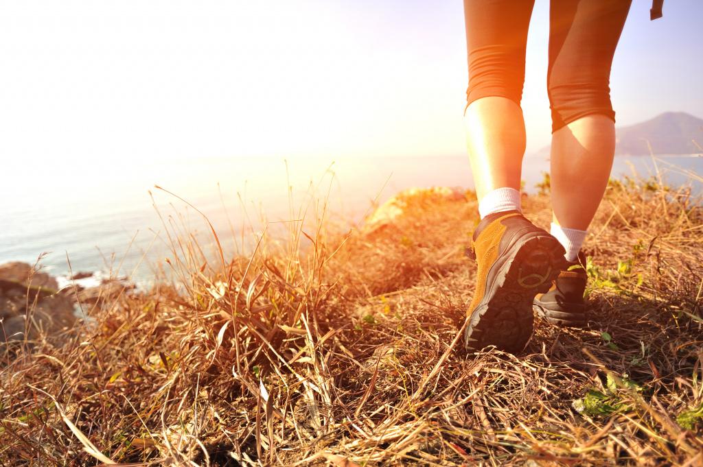 Med vandringskängor på berg med utsikt över havet