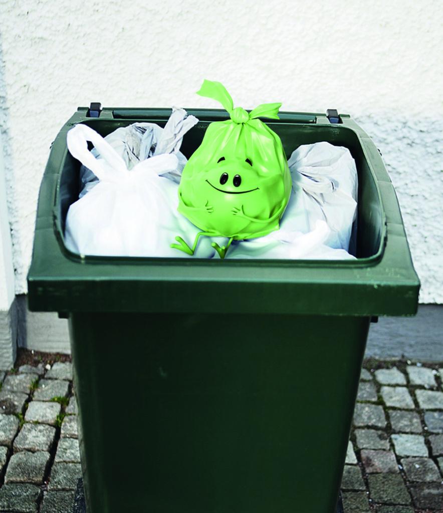 Grön soppåse i soptunna bland andra påsar