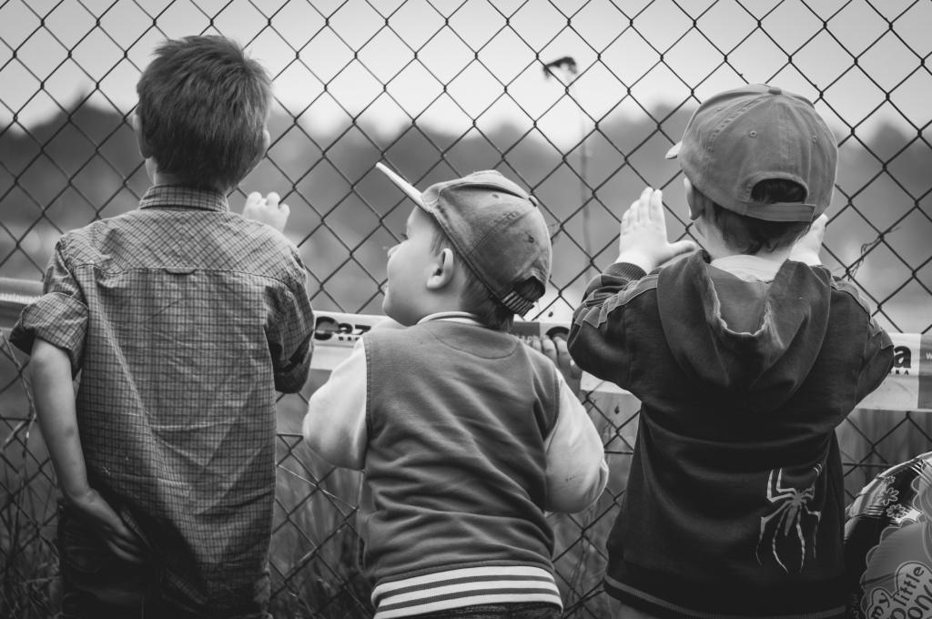 Svartvit foto på barn som står med ryggen emot för att kolla igenom ett stängsel