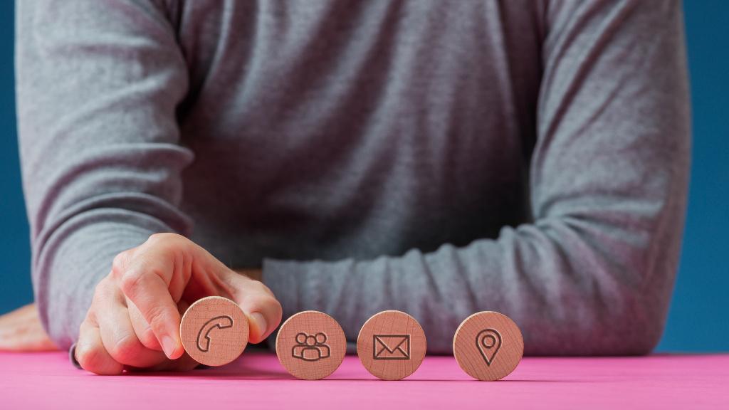 Man som placerar ikoner i trä för kontaktuppgifter