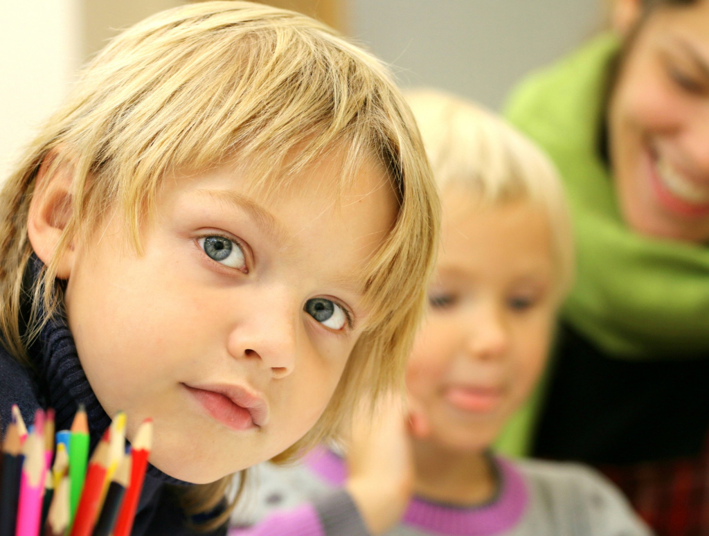 Barn med pennor på skola